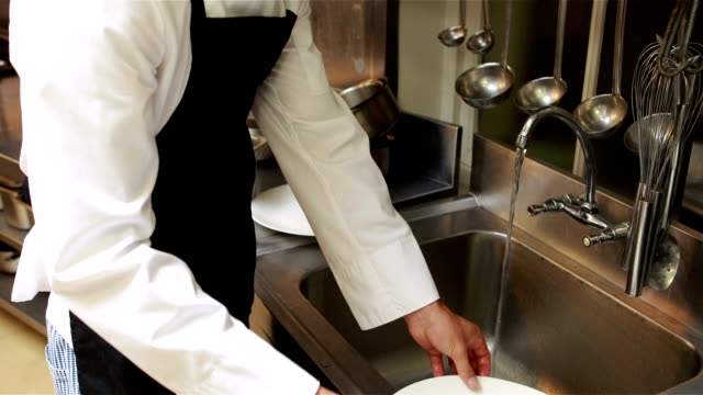 Handsome chef cleaning dishes Handsome chef cleaning dishes in the kitchen dishwasher stock videos & royalty-free footage