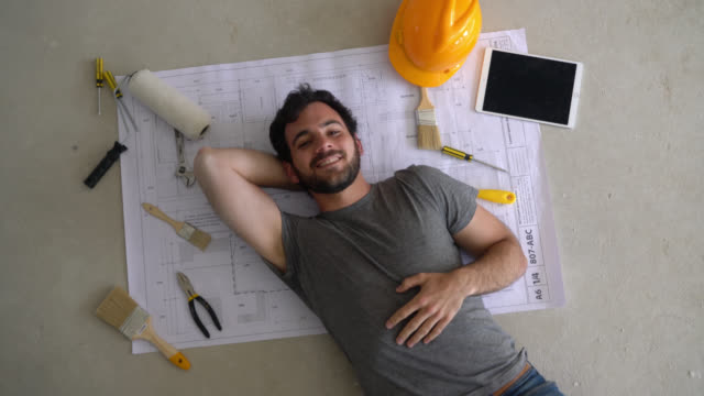 Handsome constructor lying down on floor on top of a blueprint with tools and a tablet next to him smiling at camera Handsome young constructor lying down on floor on top of a blueprint with tools and a tablet next to him smiling at camera renovation stock videos & royalty-free footage