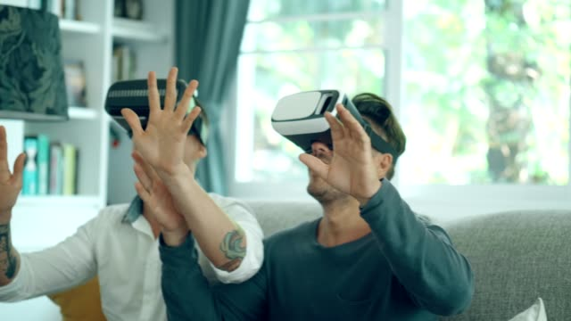 lgbt handsome couple enjoy playing virtual reality simulator for relaxation - koncentracja filmów i materiałów b-roll