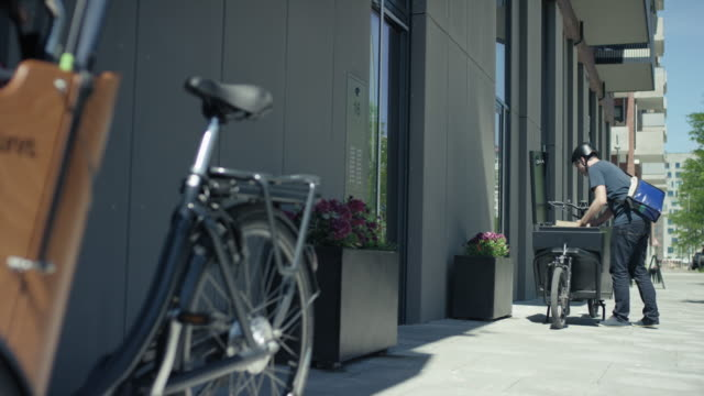 Handsome courier delivering packages to customers with his cargo bike video