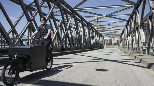 Handsome courier on cargo bike driving over a historical bridge in Hamburg video