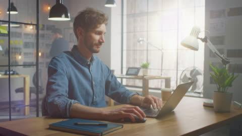 il bel maschio creativo in camicia jeans funziona su un laptop nel suo ufficio loft soleggiato. sembra figo e intelligente, ha la barba. il collega lavora con storyboard in background. office ha una grande finestra. - abbigliamento casual video stock e b–roll