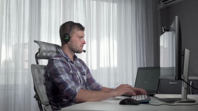 handsome customer support operator typing on a computer - shifts call centre video stock e b–roll