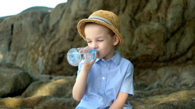 ハンサムなかわいい男の子は晴れた日にペットボトルから澄んだ水を飲みます ビデオ