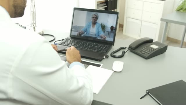 handsome doctor giving remote medical consultation with senior woman patient over internet computer telemedecine diagnostic 4k 50fps footage - telemedicine stock videos & royalty-free footage