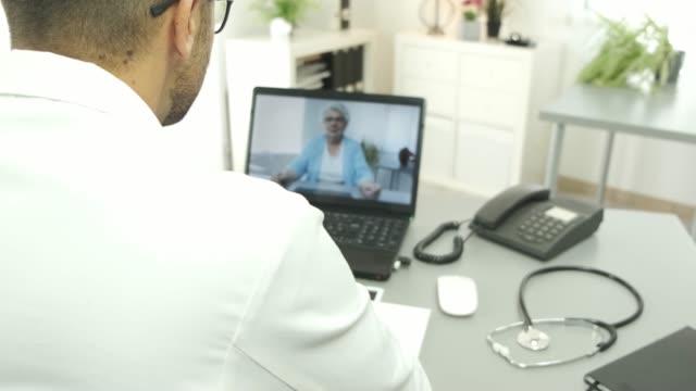 handsome doctor giving remote medical consultation with senior woman patient over internet computer telemedecine diagnostic 4K 50fps footage - vídeo