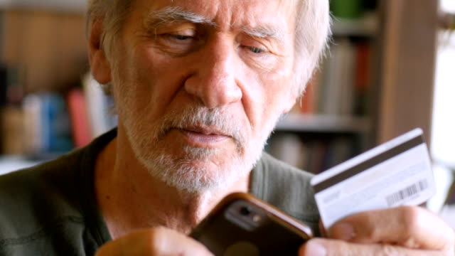 a handsome elderly man shops with credit card to make purchase on a smart phone - credit card filmów i materiałów b-roll