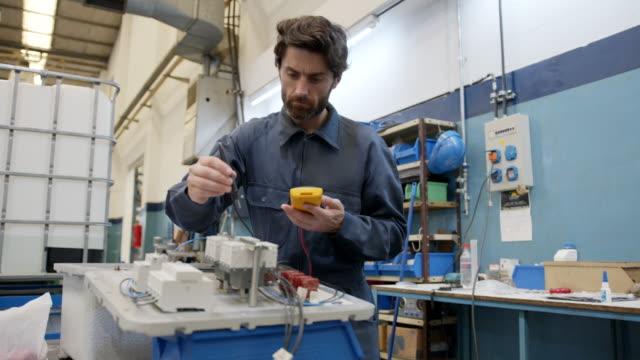 yakışıklı elektrik mühendisi bir üretim şirketinde anahtar panosu ile kontrol - parça stok videoları ve detay görüntü çekimi