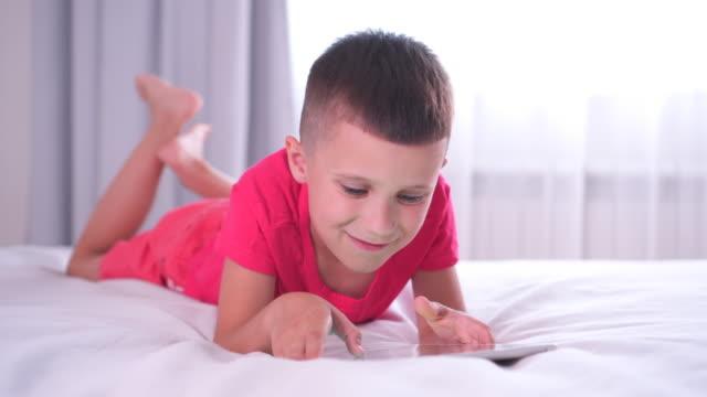 Handsome euphoric boy winning game on digital tablet video