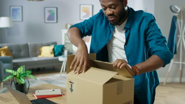 hübscher aufgeregter mann öffnet post paket karton und ist sehr glücklich mit inhalt. mann paket auspacken. - post it stock-videos und b-roll-filmmaterial