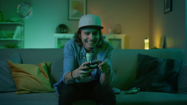 vídeos de stock e filmes b-roll de handsome excited young gamer with long hair and a cap is sitting on a couch and playing video games on a console. he plays with a wireless controller. cozy room is lit with warm and neon light. - man joystick