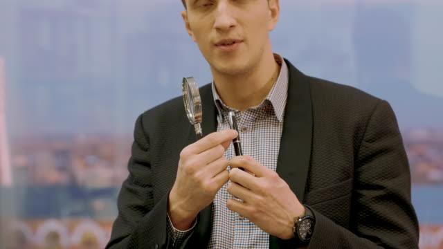 handsome expert in suit checking pen with magnifier lens, handheld shot - expert стоковые видео и кадры b-roll