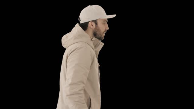 vídeos de stock, filmes e b-roll de homem bonito da moda em um casaco estiloso de inverno andando, - boné
