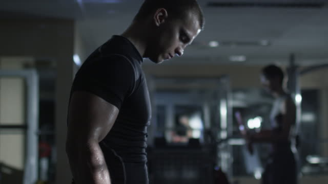 Handsome fit sporty man does dumbbell curl exercises in dark gym. video