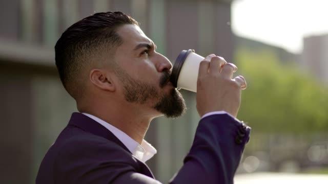 snygg fokuserad affärs man dricka från papper kopp utomhus - kostym sida bildbanksvideor och videomaterial från bakom kulisserna