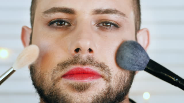 stockvideo's en b-roll-footage met knappe vrolijke of metroseksuele mens die make-up krijgt - vetschmink