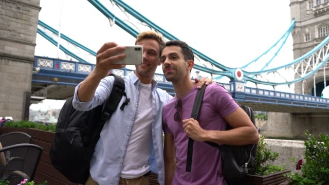 Handsome gay student couple at the London Bridge taking a selfie embracing each other smiling