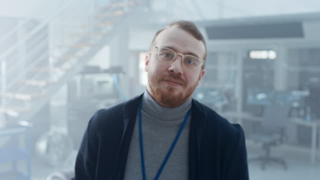 Handsome Ginger Creative Design Engineer with Beard and Glasses Poses for Camera Next to an Electric Car Chassis Prototype. In High Tech Laboratory Facility with Vehicle Frame. Handsome Ginger Creative Design Engineer with Beard and Glasses Poses for Camera Next to an Electric Car Chassis Prototype. In High Tech Laboratory Facility with Vehicle Frame. Shot on 8K RED Camera. vehicle part stock videos & royalty-free footage