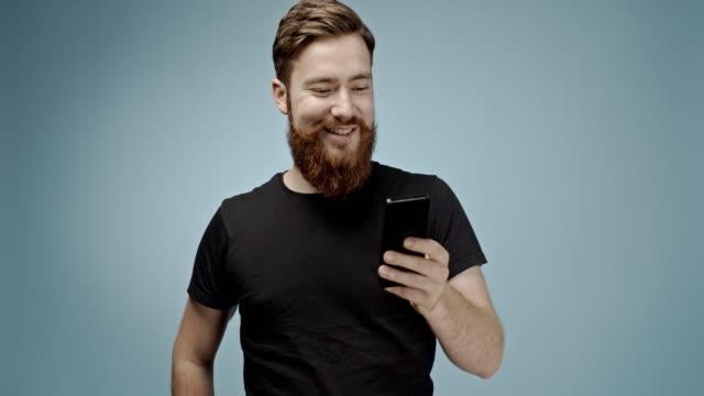 vídeos de stock, filmes e b-roll de bonito gengibre cabelo caucasiano jovem hipster homem com bigode e barba texting com sua namorada e tomar um selfie e enviá-lo com seu dispositivo de telefone inteligente. tiro em câmara lenta 4k - fundo colorido
