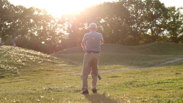 Hermoso abuelo girando alrededor de niño niño - vídeo