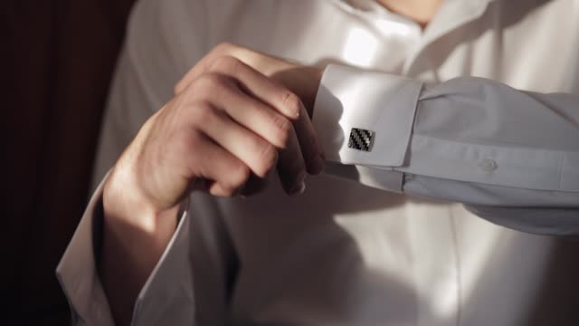 Handsome groom man fixes his cuffs on a shirt with cufflinks. Businessman Handsome groom fixes his cuffs on a shirt. White shirt with cufflinks. Wedding morning. Businessman. Close-up shot. Slow motion button down shirt stock videos & royalty-free footage
