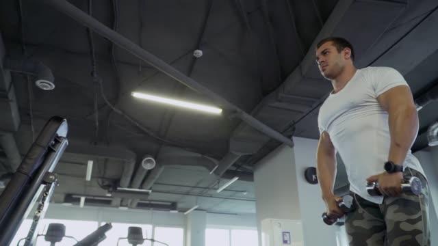 stockvideo's en b-roll-footage met knappe jongen doen oefeningen met halters in de sportschool - wit t shirt