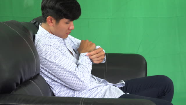 Handsome guy folds his sleeves for comfort and relaxation.