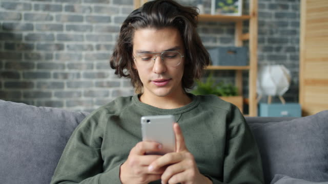 Handsome guy having fun with smartphone touching screen sitting on sofa at home video