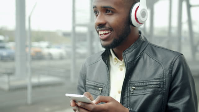 Handsome guy in headphones using smartphone laughing in city street Handsome African American guy in wireless headphones is using smartphone laughing standing alone in city street. Communication, technology and fun concept. multimedia stock videos & royalty-free footage