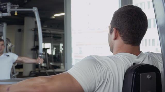 stockvideo's en b-roll-footage met knappe jongen is betrokken bij de sportschool - wit t shirt