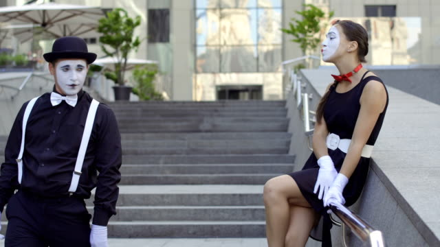 Handsome guy mime in hat give invisible bouquet of flowers to young cute girl Two funny mimes play a scene at the staircase near office center. Girl and guy gesticulates their facial expressions and hands. Young amateurs earn money showing people small funny scenes at urban streets. greasepaint stock videos & royalty-free footage