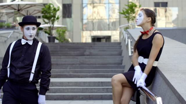 帽子でハンサムな男 mime が若いかわいい女の子に見えない花束を与える - グリースペイント点の映像素材/bロール