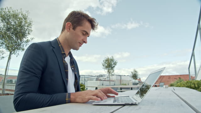 Handsome Guy Using Laptop Outside Lockdown Medium Shot Of Handsome Guy Using Laptop Outside On Table And Smiling mid adult men stock videos & royalty-free footage