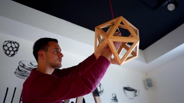 handsome handyman ersätter en glöd lampa i sitt arbets kontor - rådig bildbanksvideor och videomaterial från bakom kulisserna
