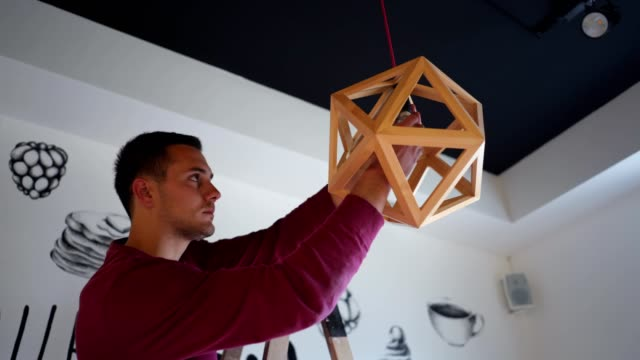 vídeos de stock e filmes b-roll de handsome handyman replacing a lightbulb in his work office - bricolage