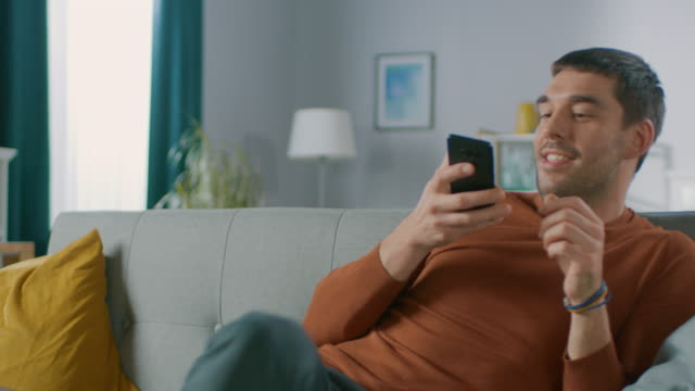 handsome happy man at home, sits down on a sofa while using smartphone, does various touching and swiping gestures. man relaxing with mobile phone in his cozy living room. - guy sofa video stock e b–roll