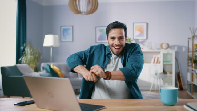 잘생긴 행복 남자 않습니다 재미 있는 댄스 루틴 거실에 그의 책상에 앉아있는 동안. - 잘생김 스톡 비디오 및 b-롤 화면