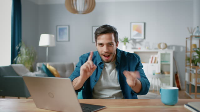Handsome Happy Man Does Funny Dance Routine while Sitting at His Desk in the Living Room.