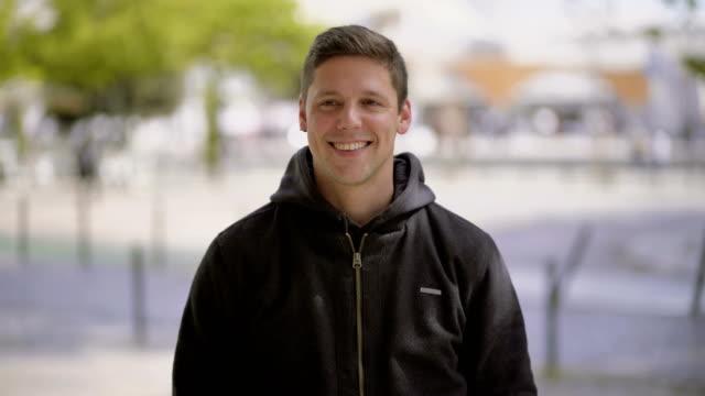 vídeos de stock e filmes b-roll de handsome happy young man looking at camera - homem casual standing sorrir