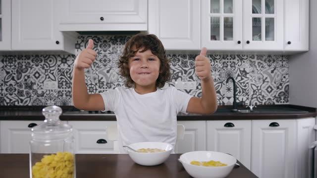 ハンサムな空腹の小さな男の子がミルクで彼のトウモロコシのフレークを食べて、指で「それは良いです」ジェスチャーを作ります - 4歳から5歳点の映像素材/bロール