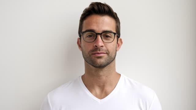 handsome in specs - sfondo bianco video stock e b–roll