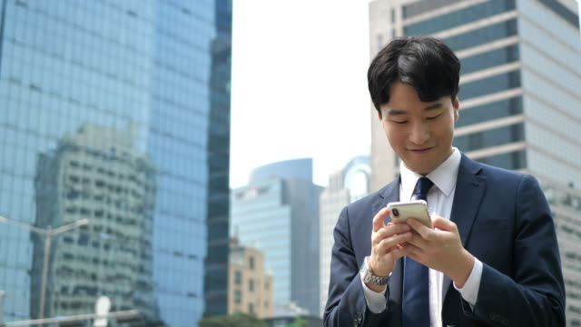 handsome korean businessman using mobile app for electronic banking - cultura coreana video stock e b–roll