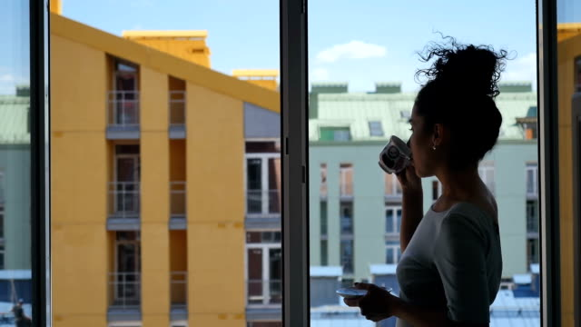 Bonita senhora beber café perto da janela - vídeo