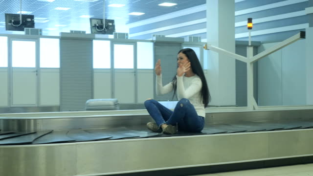 Handsome lady sits at the luggage conveyor and moves along video