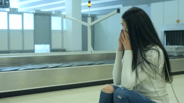 handsome lady waits for her luggage at the airport and talks on the phone - donna valigia solitudine video stock e b–roll