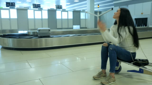 handsome lady waits for her luggage at the airport - donna valigia solitudine video stock e b–roll