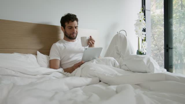 stockvideo's en b-roll-footage met knappe latijns-amerikaanse mens die op bed ontspant dat thee drinkt en iets op tablet leest - dekbed