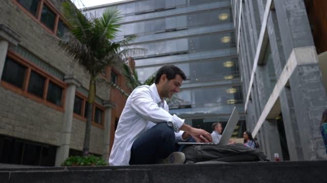 vidéos et rushes de beau étudiant latino-américain fait un devoirs sur ordinateur portable air heureux - vue en contre plongée verticale