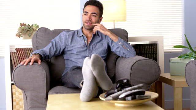 Handsome Latino sitting at home thinking video
