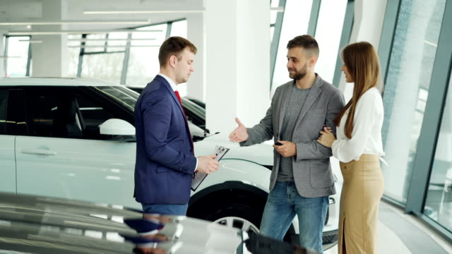 Handsome male car buyer is getting key fob from friendly salesman and shaking hands with him then kissing and hugging his attractive girlfriend while standing beside auto. Handsome male car buyer is getting key fob from friendly salesman and shaking hands with him then kissing and hugging his attractive girlfriend while standing beside new auto. car shopping stock videos & royalty-free footage